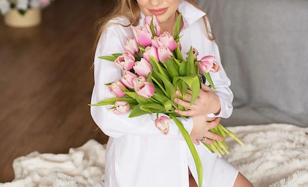 Ciężarna dziewczyna na lekkim tle z kwiatami. zdjęcie bez twarzy w ramce.
