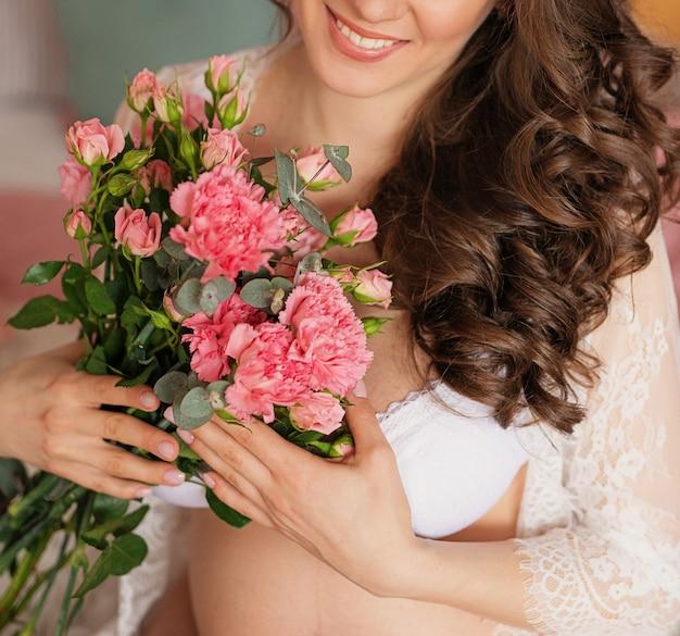Ciężarna dziewczyna na lekkim tle z kwiatami