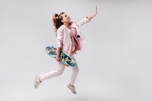 Ciężarna dziewczyna w różowym garniturze z deskorolką w dłoniach skacze na szarym tle