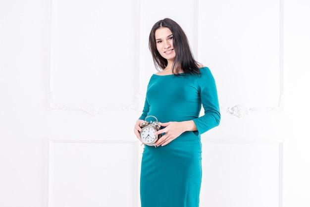 Ciężarna dziewczyna w sukience, z zegarkiem w dłoniach. zdjęcie wysokiej jakości