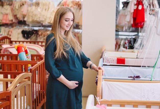 Ciężarna dziewczyna wybiera łóżeczko dziecięce w sklepie.