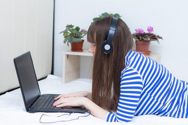 Ciężarna dziewczyna z laptopem na łóżku.