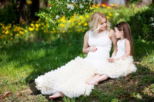 Ciężarna mama i jej mała córka bawią się na świeżym powietrzu. portret wygląd rodziny