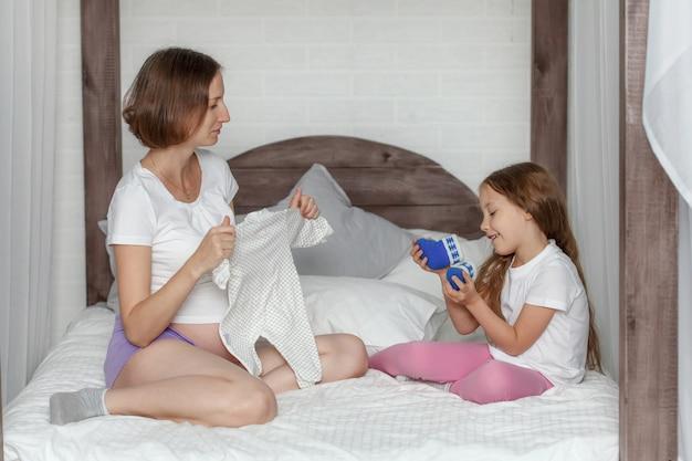 Ciężarna matka i córka przygotowuje odzież dla noworodka