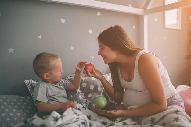 Ciężarna matka i mały syn jedzą rano jabłko i brzoskwinię w łóżku. nieformalny styl życia w sypialni.