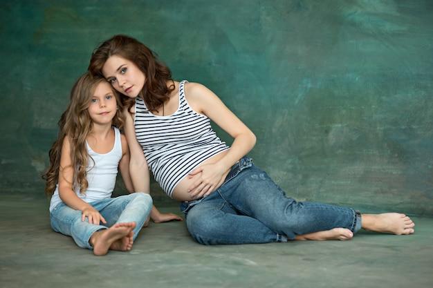 Ciężarna matka z nastoletnią córką. rodzinny pracowniany portret nad błękitnym tłem