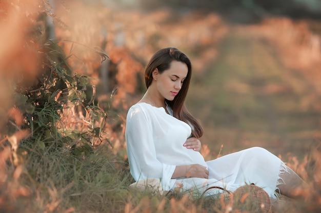 Ciężarna młoda dziewczyna w białej długiej sukni siedzi na zielonej polanie.