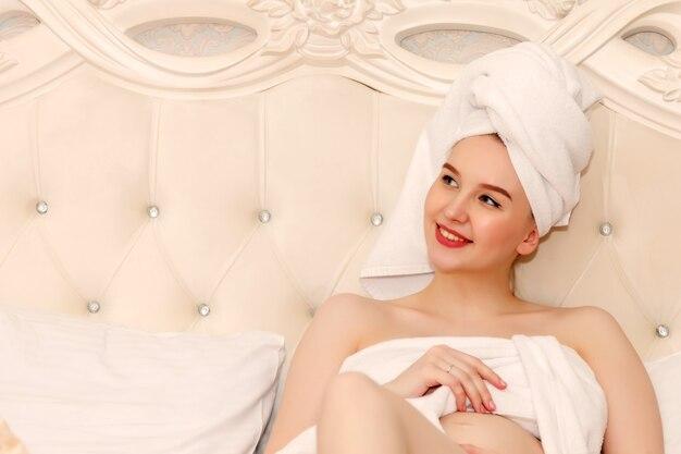 Ciężarna młoda kobieta słowiański wygląd po prysznicu, leżąc na łóżku, przytulając swój zaokrąglony brzuch w pokoju hotelowym.