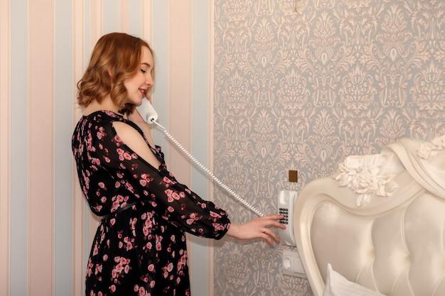 Ciężarna młoda kobieta słowiański wygląd w sukni stoi przed ścianą z słuchawką telefonu w pokoju hotelowym.