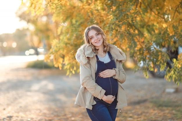 Ciężarna młoda matka chodzi jesienią w parku z żółtymi drzewami