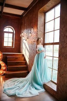 Ciężarna panna młoda blondynka przygotowuje się do zostania matką i żoną. długa turkusowa sukienka na dziewczęcym body. kręcone włosy i piękny uśmiech na twarzy kobiety. dwa miesiące przed urodzeniem