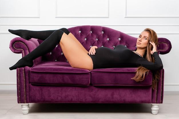 Ciężarna piękna kobieta pozuje kłamać na kanapie, trzyma jej brzucha