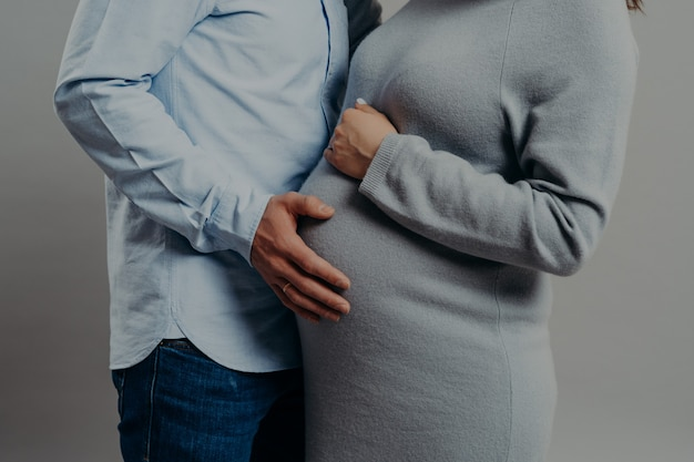 Ciężarna żona ubiera się w pozy obok męża, który dotyka jej dużego brzucha. przyszła mama i ojciec czekają na nowego członka rodziny. koncepcja rodzicielstwa