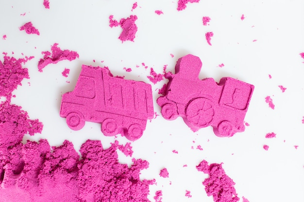 Ciężarówka i pociąg robić z różowym kinetycznym piaskiem na białym tle.