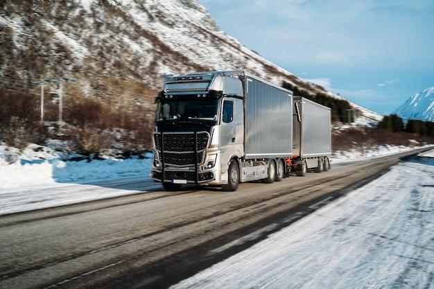 Ciężarówka jeżdżąca po zaśnieżonej autostradzie w słoneczny dzień. koncepcja bezpieczeństwa drogowego zimą.