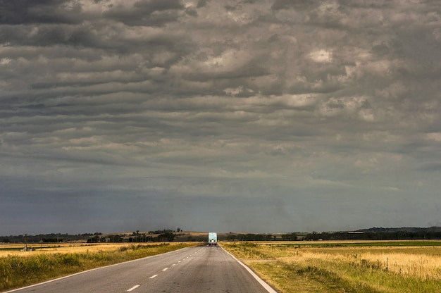 Ciężarówka na drodze otoczonej pustymi polami pod zachmurzonym niebem
