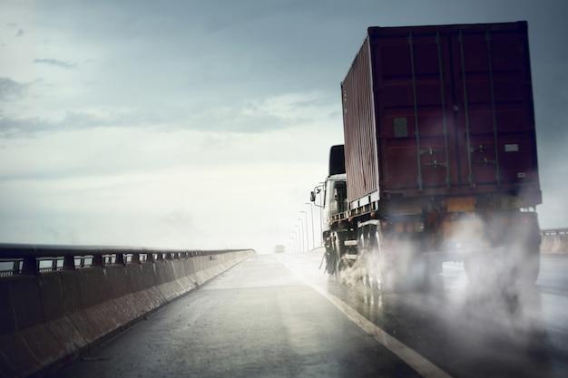 Ciężarówka porusza się szybko na mokrej drodze po ulewnym deszczu, złych warunkach pogodowych
