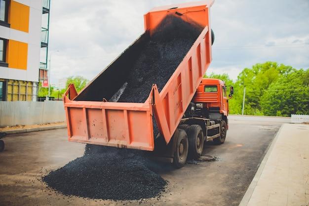 Ciężarówka rozładowuje świeży asfalt do rozrzutnika na dużej drodze w mieście
