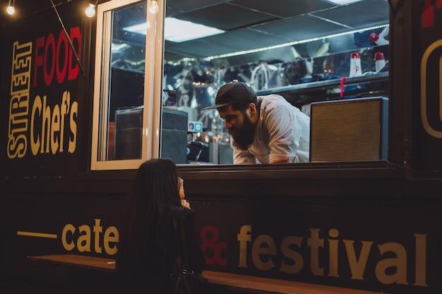 Ciężarówka spożywcza z hot-dogami i hamburgerami. brutalny brodaty szef kuchni