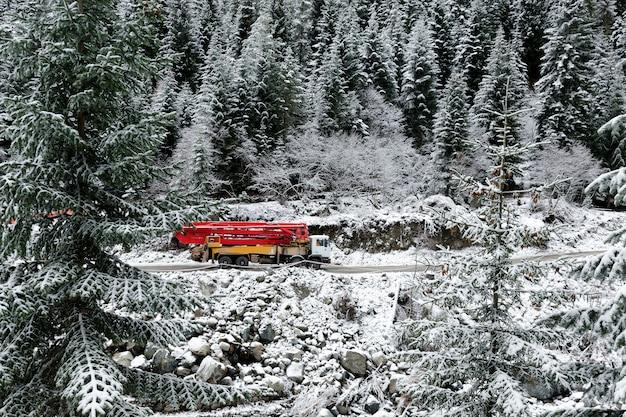 Ciężarówka z dźwigiem jedzie górską drogą, pośród zaśnieżonych wysokich świerków.