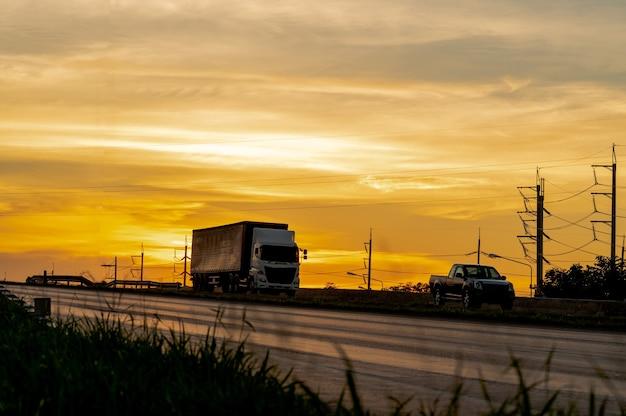 Ciężarówka z ładunkiem na autostradzie transportu drogowego o zachodzie słońca w lecie