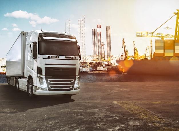 Ciężarówka z przyczepą na doku portu handlowego o zachodzie słońca