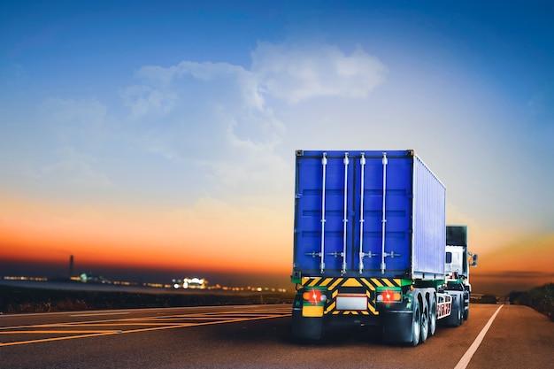 Ciężarówka z przyczepą z kontenerem jeżdżąca po autostradzie do osiedla przemysłowego w godzinach wieczornych
