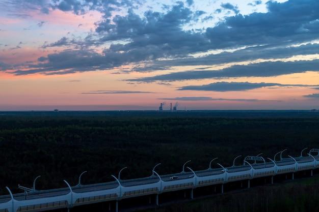 Ciężarówki i samochody jadące autostradą skręcają w kierunku horyzontu w jesiennym, letnim krajobrazie z pastelowymi, niesamowitymi chmurami na niebie. skopiuj miejsce