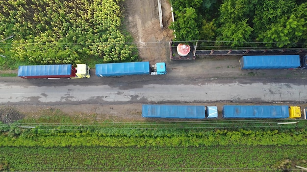 Ciężarówki są zaparkowane na poboczu wiejskiej drogi utwardzonej. widok z góry na ciągniki z przyczepą.