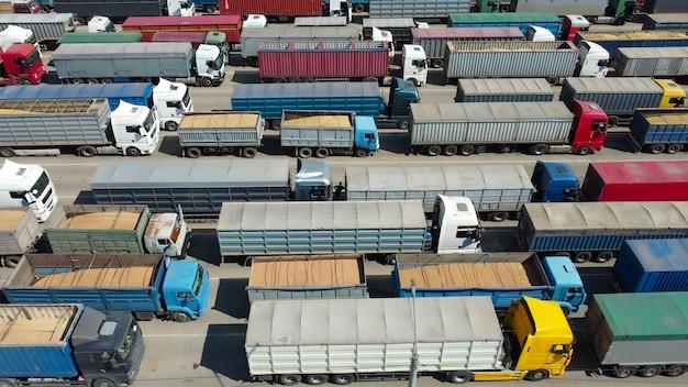 Ciężarówki z kontenerami i przyczepy w porcie czekają na rozładunek.