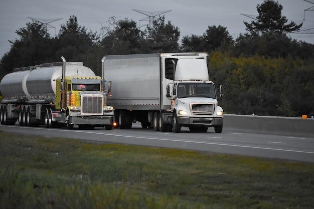 Ciężarówki z przyczepą poruszające się po drodze otoczonej pięknymi zielonymi drzewami
