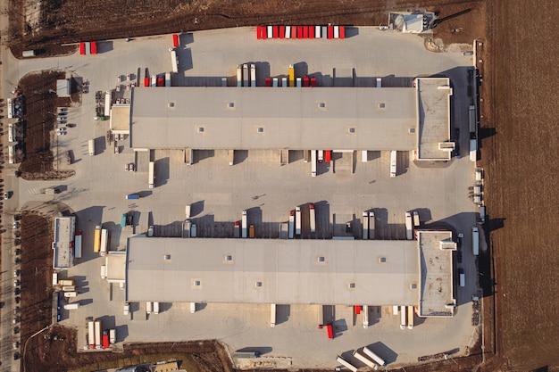 Ciężarówki z przyczepami czekają na załadunek towaru do transportu w magazynie załadunkowym. widok z góry z lotu ptaka. duży terminal ładunków tranzytowych z parkingami, ciężarówkami i przyczepami.