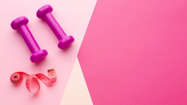 Ciężary i metr na różowym tle z kopii przestrzenią