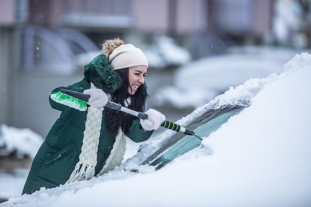 Ciężka praca podczas skrobania szyb samochodowych z lodu i śniegu podczas mroźnej zimy.