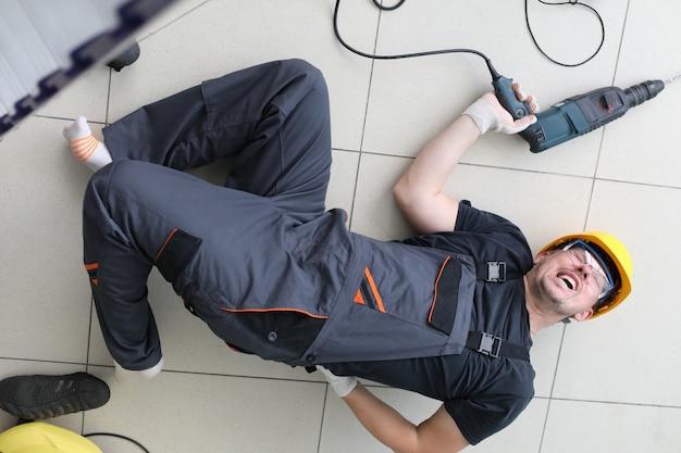 Ciężki ból w plecach budowniczego, mężczyzna leży na podłodze.