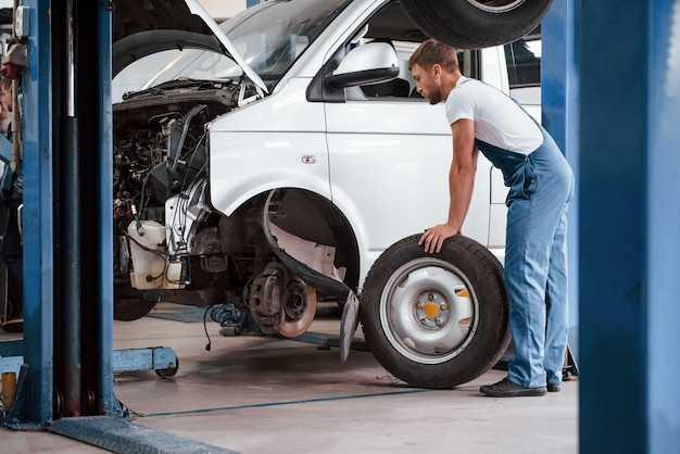 Ciężki pojazd. pracownik w niebieskim mundurze pracuje w salonie samochodowym.