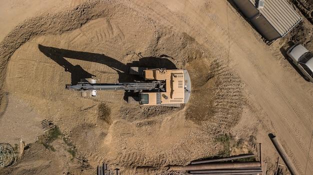 Ciężki sprzęt wyrównuje teren, przesuwa i spłaszcza czerwoną gliniastą glebę.