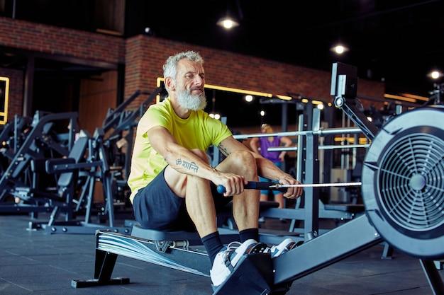 Ciężki trening dojrzały atletyczny mężczyzna w stroju sportowym, ćwiczący na maszynie do wiosłowania na siłowni