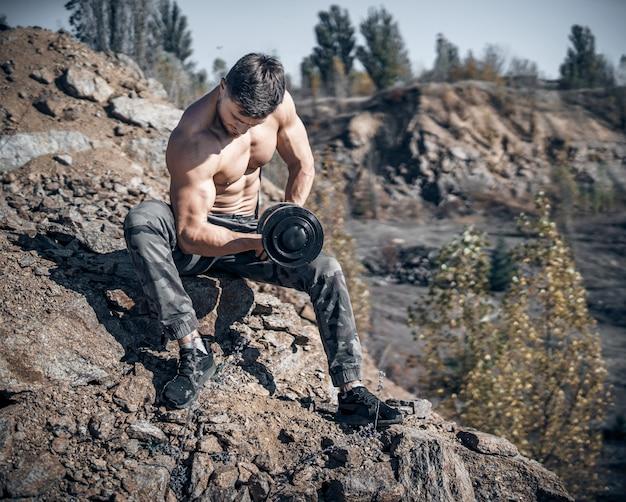 Ciężki trening w kamieniołomie. intensywny trening. silny atrakcyjny kulturysta. styl życia. biały krajobraz.