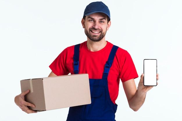 Ciężkiego pracownika kuriera mężczyzna pokazuje telefon komórkowego i pudełko