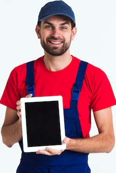 Ciężkiego pracownika kuriera mężczyzna trzyma cyfrową pastylkę