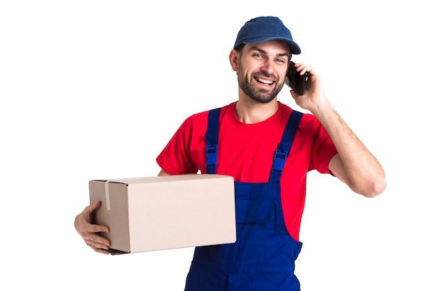 Ciężkiego pracownika kuriera mężczyzna trzyma pudełko i opowiada na telefonie