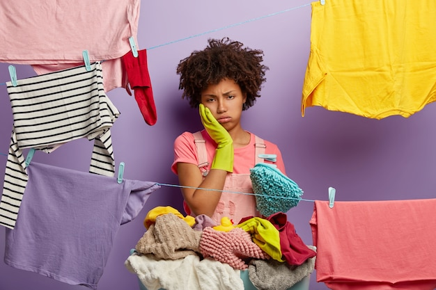 Ciężko pracująca zmęczona gospodyni domowa wzdycha ze zmęczenia, dotyka policzka, nosi gumowe rękawiczki, stoi przy sznurkach z powieszonymi czystymi ubraniami, znudzi się codzienną rutyną w domu, myje przez cały dzień