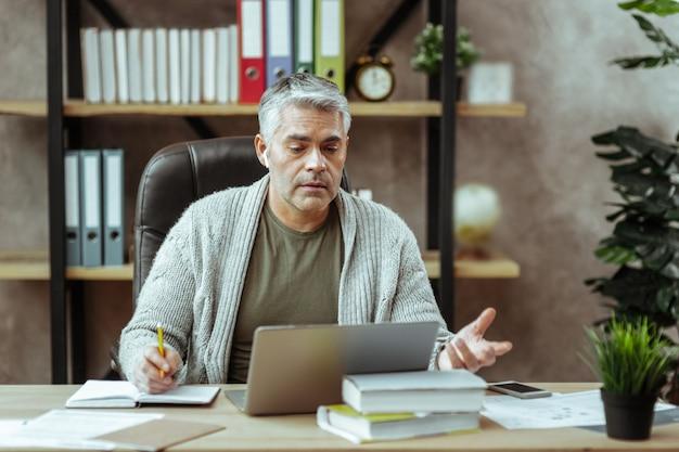 Ciężko pracujący biznesmen. poważny miły człowiek siedzący przed laptopem podczas robienia notatek w notatniku