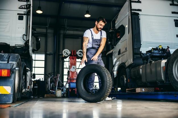 Ciężko pracujący mechanik toczy oponę, aby wymienić ją na ciężarówce. jest w garażu firmy importowo-eksportowej.