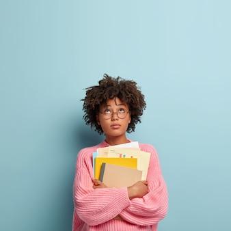 Ciężko pracujący student skupiony na sobie, ma przy sobie papiery, podręcznik i notatnik