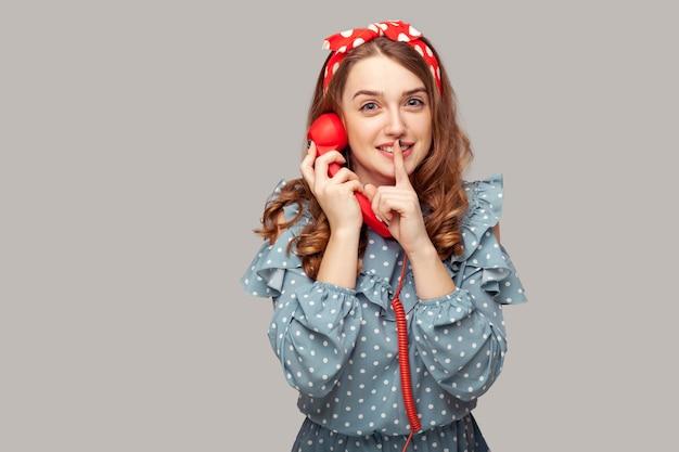 Ciii, bądź cicho śliczna pinup girl trzyma słuchawkę telefonu patrząc na kamerę