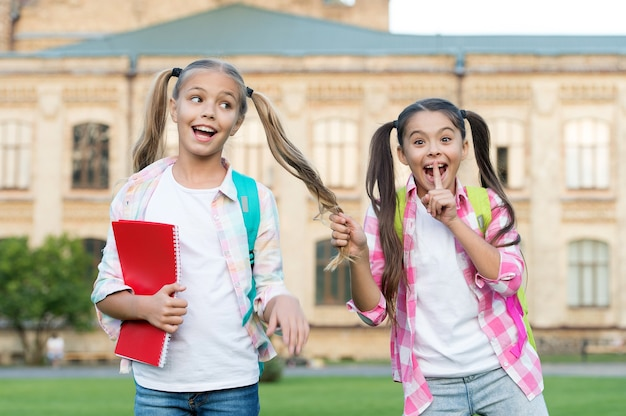 Ciii dziewczyny sekret. szczęśliwe dzieci zachowują tajemnicę. mała dziewczynka robi tajny gest. przyjaciele i przyjaźń. cisza i cisza. powrót do szkoły. edukacja i nauka. dzień wiedzy. mamy swój mały sekret.