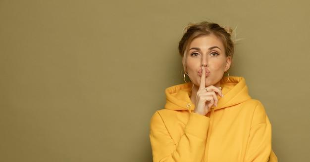 Ciii! portret ładna tajemnicza dziewczyna w przypadkowym żółtym stroju pokazuje cisza szyldowego mienia forefinger na koloru tle.