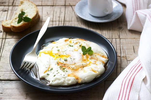 Cilbir, jajko sadzone w jogurcie z przyprawionym masłem i ziołami, podawane z chlebem i filiżanką kawy.